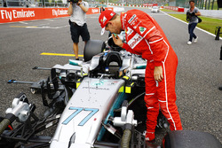 Sebastian Vettel, Ferrari, looks at the car of Valtteri Bottas, Mercedes AMG F1 W08