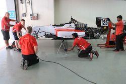 Een monteur werkt aan de wagen van Mick Schumacher