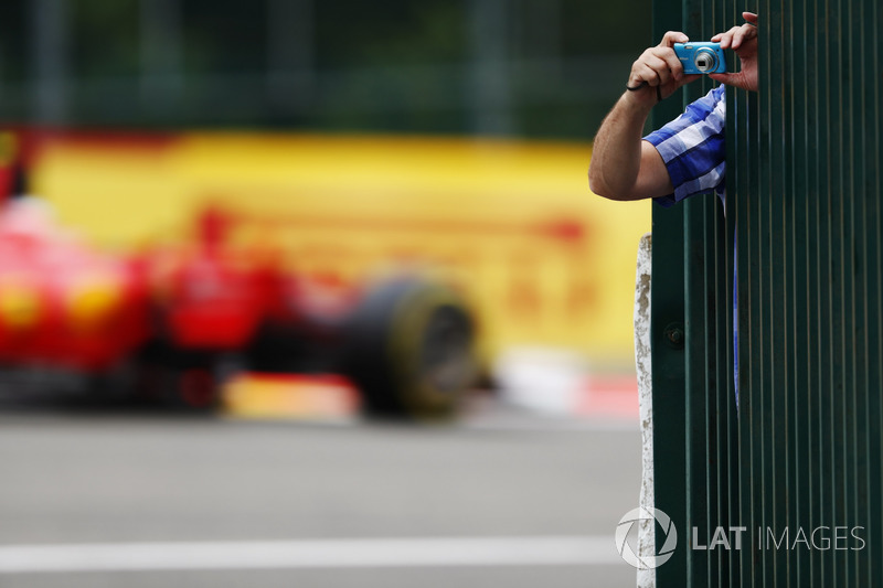 A fan leans out to take some photos as Kimi Raikkonen, Ferrari SF70H, passes through the background