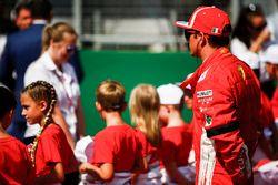 Kimi Raikkonen, Ferrari, on the grid with the grid kids prior to the start