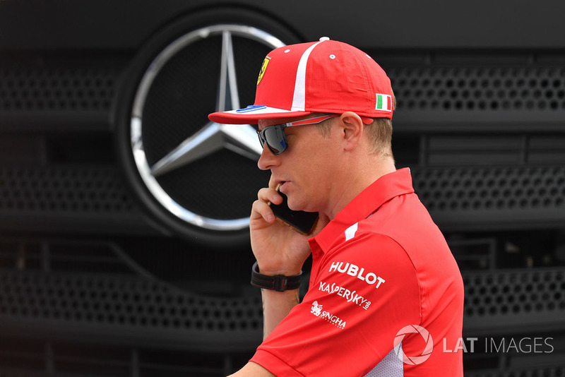 Kimi Raikkonen, Ferrari on his phone infront of Mercedes Logo