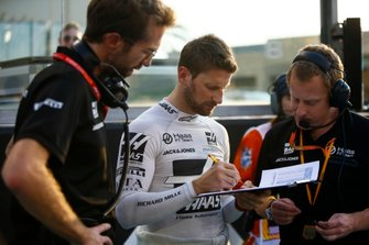 Romain Grosjean, Haas F1, works with colleagues on the grid