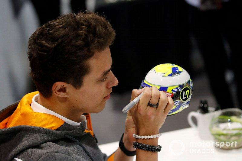 Lando Norris, McLaren signs a miniature replica helmet