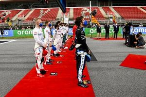 The drivers stand in line for the national anthem on the grid prior to the start