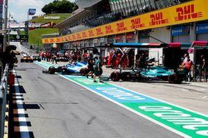 Esteban Ocon, Alpine A521, andLance Stroll, Aston Martin AMR21 , leave the garage