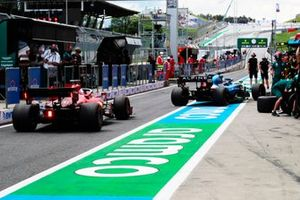 Fernando Alonso, Alpine A521, and Charles Leclerc, Ferrari SF21, in the pit lane