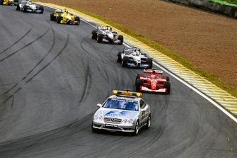 The safety car leads Michael Schumacher, Ferrari F2001, Juan Pablo Montoya, Williams FW23 BMW, David Coulthard, McLaren MP4-16 Mercedes, and Jarno Trulli, Jordan EJ11 Honda