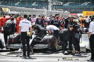 Lewis Hamilton, Mercedes-AMG F1, prepares on the grid as mechanics prepare his car