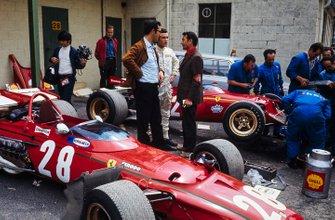 Jacky Ickx y Mauro Forghieri diseñador de Ferrari con un periodista en el paddock