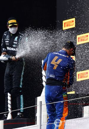 Lewis Hamilton, Mercedes, 2nd position, and Lando Norris, McLaren, 3rd position, spray Champagne on the podium