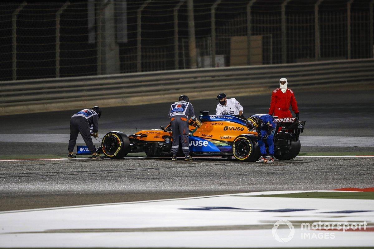 Carlos Sainz Jr., McLaren, mira la parte trasera de su coche mientras los oficiales trabajan para recuperarlo