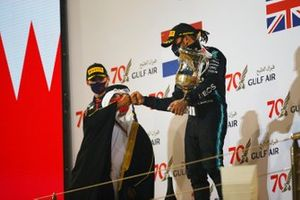 Lewis Hamilton, Mercedes-AMG F1, fist bumps a Bahraini dignitary on the podium as Max Verstappen, Red Bull Racing, looks on