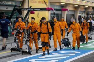 McLaren mechanics head to the grid
