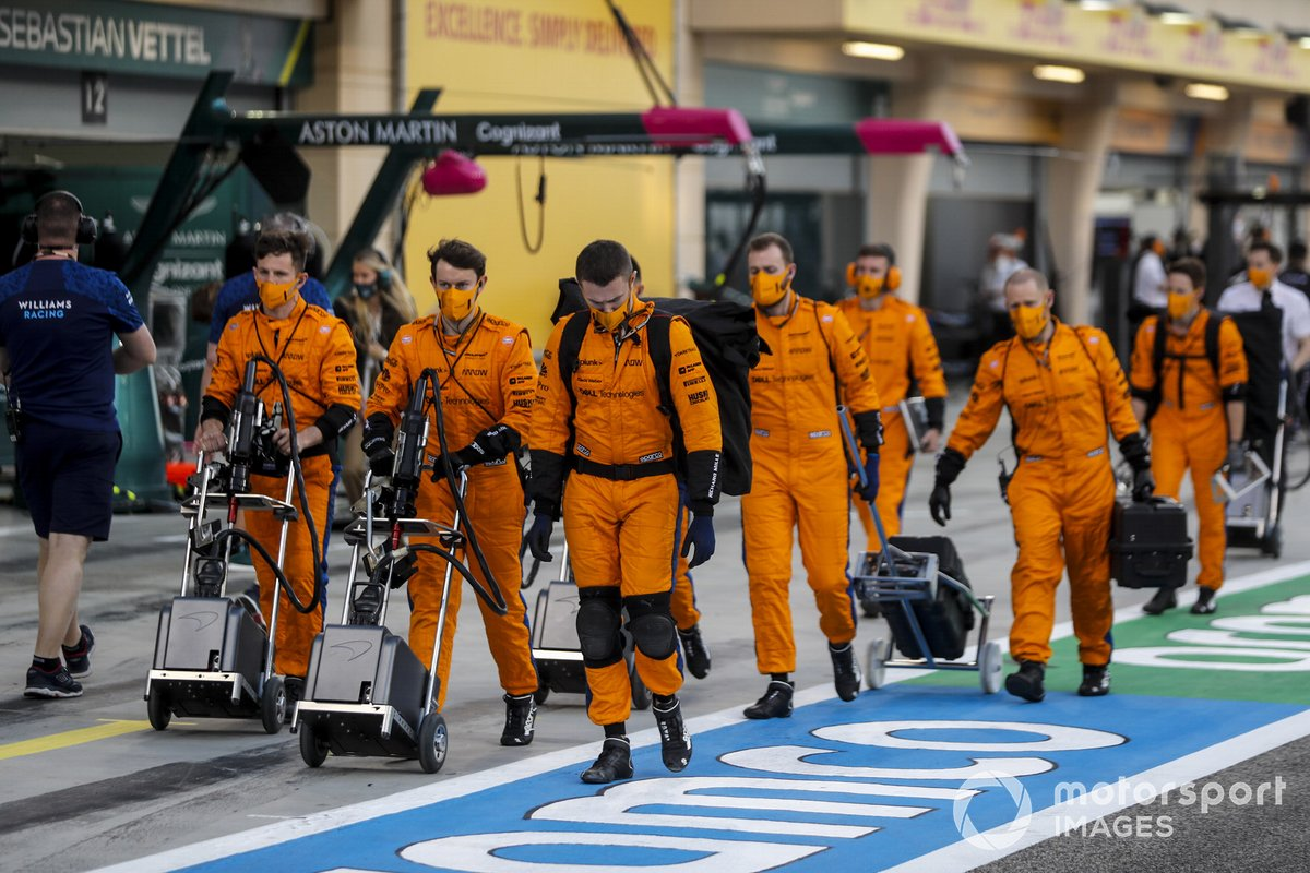 Los mecánicos de McLaren se dirigen a la parrilla