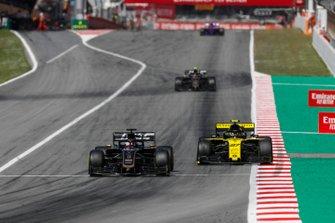 Romain Grosjean, Haas F1 Team VF-19, leads Nico Hulkenberg, Renault R.S. 19, and Kevin Magnussen, Haas F1 Team VF-19