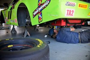 Crew members work on the #11 TA2 Dodge Challenger driven by Brian Swank of Stevens Miller Racing