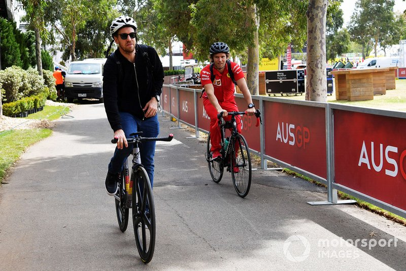 Sebastian Vettel, Ferrari, arrives at the track on a bicycle