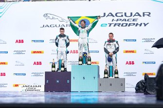 Sérgio Jimenez, 1st position, celebrates on the podium, draped in a Brazilian flag. Alongside is Bryan Sellers, 2nd position, Simon Evans, 3rd position