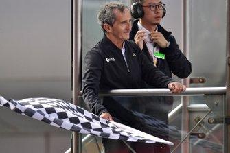 Alain Prost damalı bayrağı sallıyor