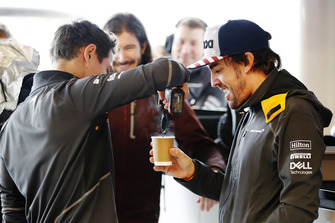 Lando Norris, McLaren, stirs a cup of tea with a power tool for Fernando Alonso, McLaren, as IndyCar driver JR Hildebrand watches in the garage.