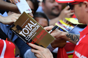 Kimi Raikkonen, Ferrari signs autograph for a fan in Ross Brawn, Formula One Managing Director of Motorsports book Total Competition