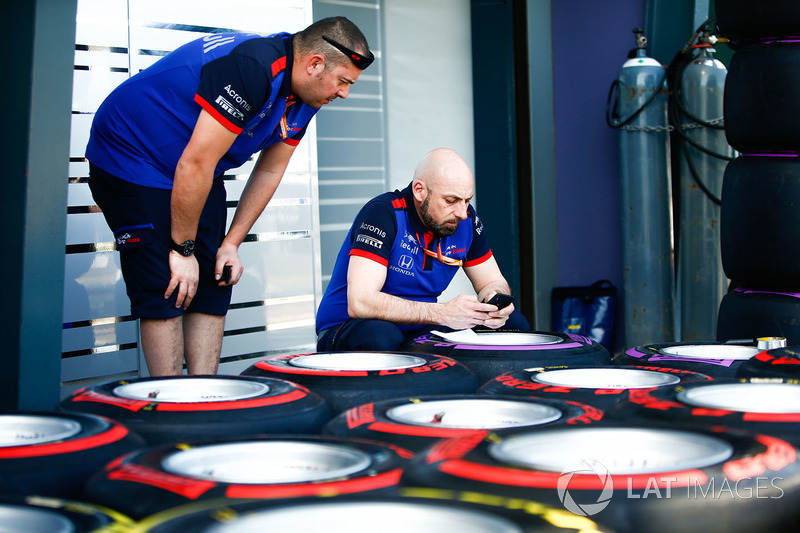 Los ingenieros de Scuderia Toro Rosso etiquetan las llantas blandas y supersoft Pirelli en el pitlane