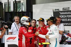 Le vainqueur Sebastian Vettel, Ferrari, est salué par le second Lewis Hamilton, Mercedes AMG F1, avec le troisième Kimi Raikkonen, Ferrari