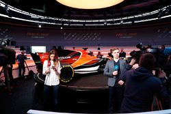 Reporters are filmed in front of the McLaren MCL32