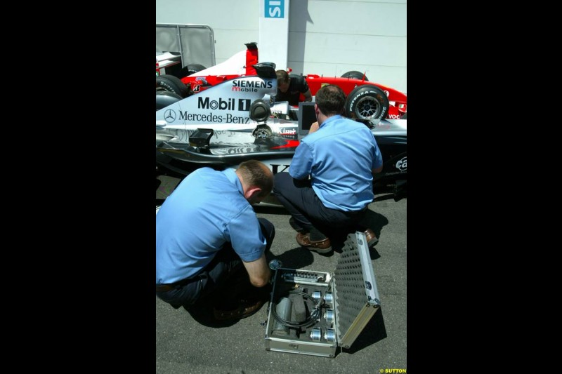 The FIA inspect Kimi Raikkonen's McLaren Mercedes MP4/17 in parc ferme post qualifying. French Grand Prix, Magny-Cours, France, 20 July 2002.