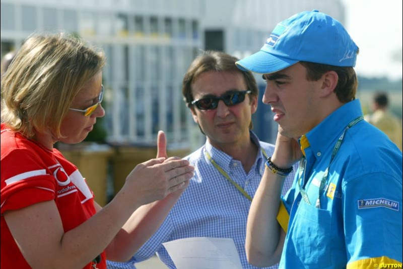 Michael Schumacher's press officer Sabine Kehm talks to Renault's Fernando Alonso. Saturday Free Practice, French Grand Prix, Magny Cours, France, July 20th 2002.