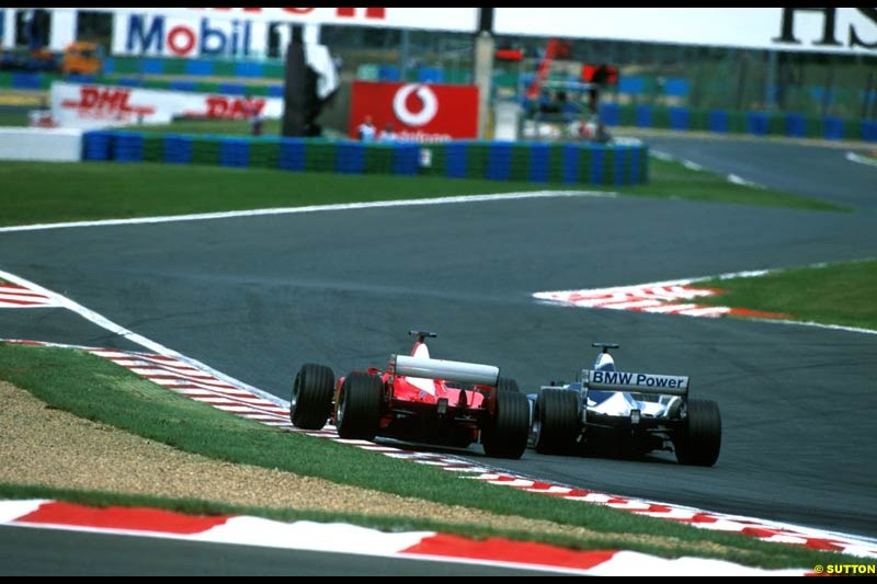 Michael Schumacher, Ferrari F12002 and Juan Pablo Montoya, Williams BMW FW24, fight for position. French Grand Prix, Magny Cours, France, July 21st 2002.