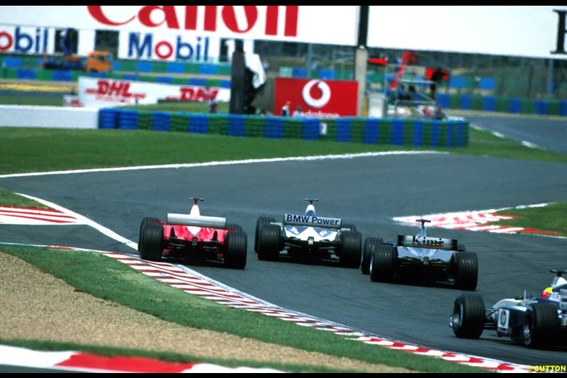 Juan Pablo Montoya, Williams BMW FW24, Michael Schumacher, Ferrari F2002 and Kimi Raikkonen, McLaren, fight for position. French Grand Prix, Magny Cours, France, July 21st 2002.