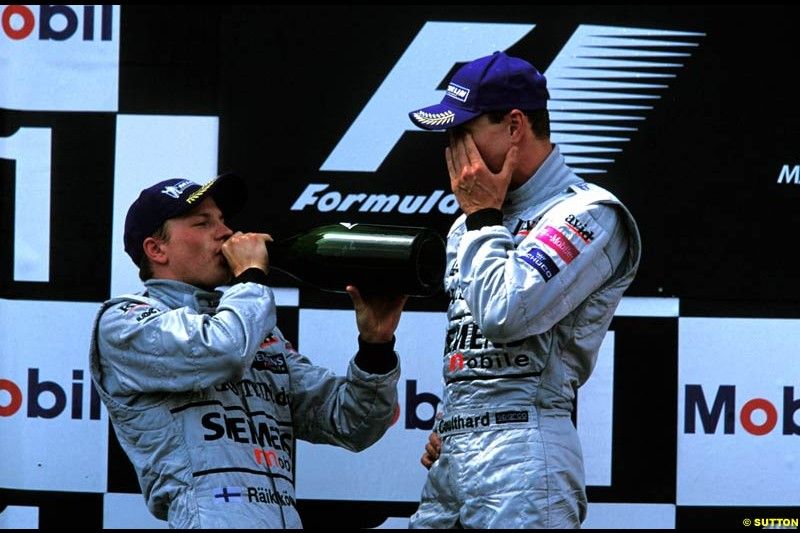 Kimi Raikkonen and David Coulthard, McLaren, celebrate second and third on the podium. French Grand Prix, Magny Cours, France, July 21st 2002.