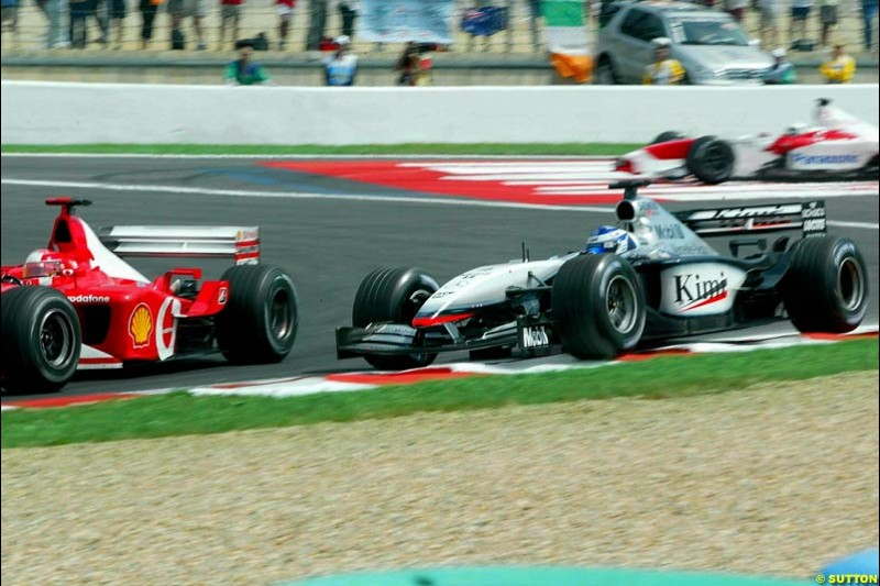 Michael Schumacher, Ferrari, passes Kimi Raikkonen, McLaren, for the lead of the French Grand Prix, Magny Cours, France, July 21st 2002.
