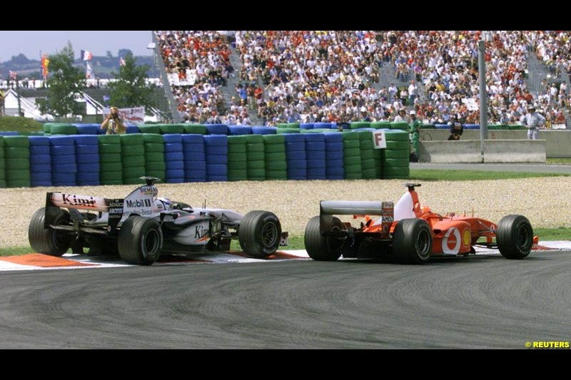 Michael Schumacher passes Kimi Raikkonen for the lead four laps before the end of the French Grand Prix, Magny Cours, France, July 21st 2002.