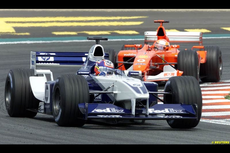 Juan Pablo Montoya, Williams, leads Michael Schumacher, Ferrari, and the start of the French Grand Prix, Magny Cours, France, July 21st 2002.