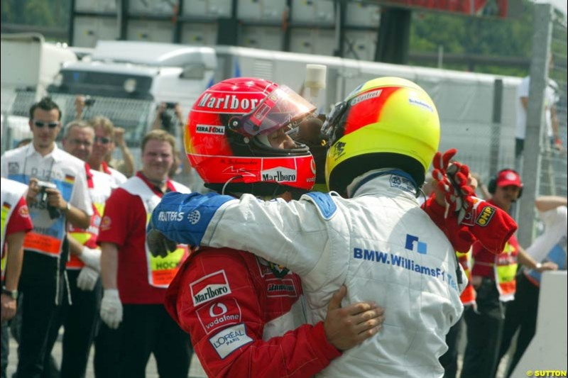 Michael Schumacher, Ferrari, and Ralf Schumacher, Williams, embrace after both qualify on the front row. German Grand Prix, Hockenheim, Germany, July 27th 2002.