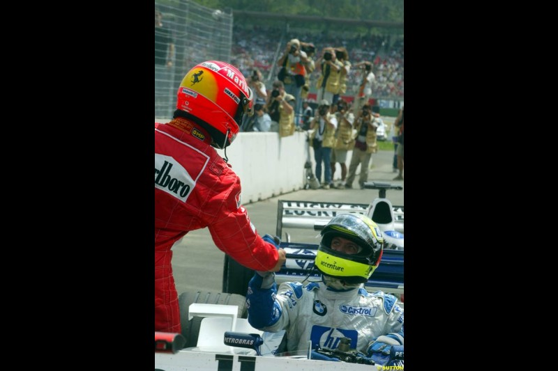 Michael Schumacher, Ferrari, congratulates brother Ralf Schumacher, Williams, after he claimed second place in Qualifying. German Grand Prix, Hockenheim, Germany, July 27th 2002.