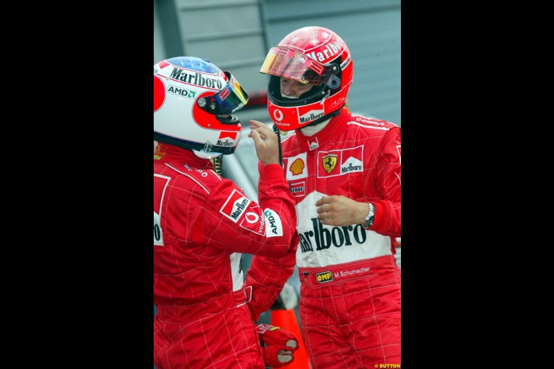 Michael Schumacher, Ferrari, chats to team mate Rubens Barrichello after qualifying. Belgian Grand Prix, Spa-Francorchamps, Belgium, August 31st 2002.