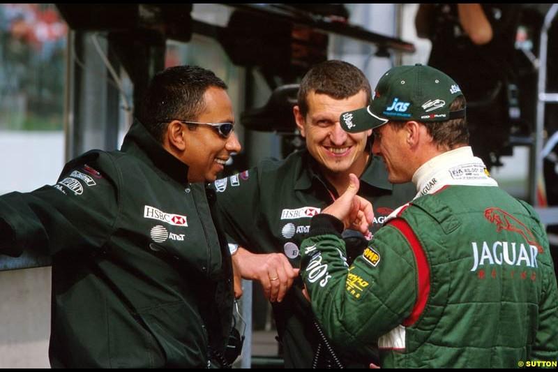 Eddie Irvine chats with Nav Sidduh, Jaguar Press Officer, and Gunther Steiner, Jaguar Technical Director. Belgian Grand Prix, Spa-Francorchamps, Belgium, September 1st 2002.