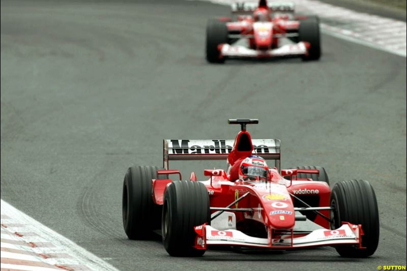Rubens Barrichello, Ferrari, briefly leads team mate Michael Schumacher during pit stops. Belgian Grand Prix, Spa-Francorchamps, Belgium, September 1st 2002.