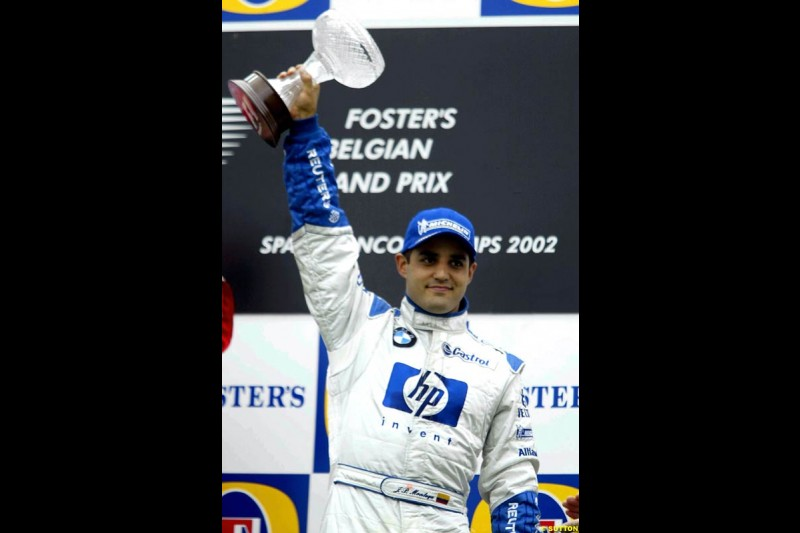 Juan Pablo Montoya, Williams, celebrates third on the podium. Belgian Grand Prix, Spa-Francorchamps, Belgium, September 1st 2002.