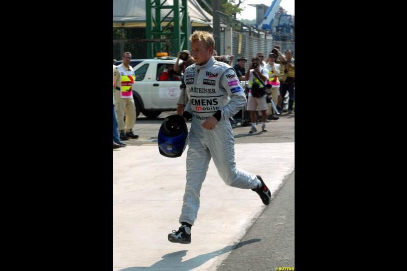 Kimi Raikkonen, McLaren, runs back to the pits after his collision with Takuma Sato, Jordan, during Qualifying. Italian Grand Prix, Monza, Italy. September 14th 2002.