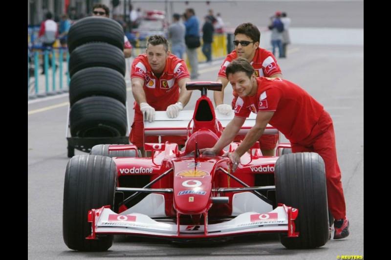 Ferrari mechanics push a car. United States GP, Indianapolis, United States. September 26th 2002.