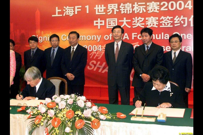 Formula One chief Bernie Ecclestone and Juan Wei, Deputy Manager of the Shanghai International Circuit Co Ltd, sign documents at a ceremony in Shanghai, China, October 21, 2002. Ecclestone signed an agreement to help the city host F1 Grand Prix races from 2004 to 2010.