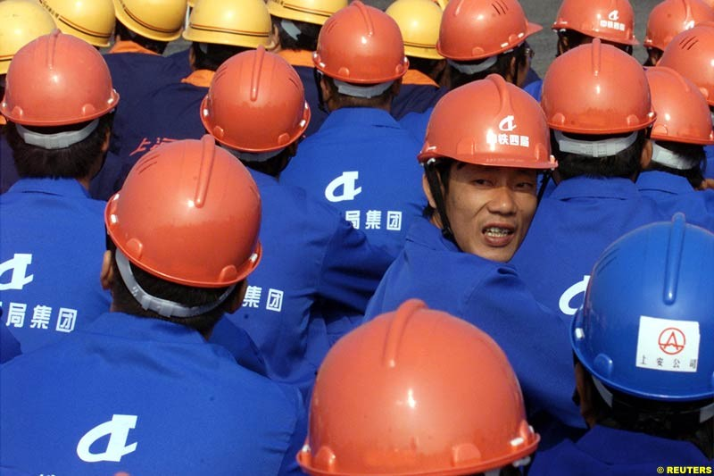 Chinese workers watch the Shanghai Circuit ground-breaking ceremony October 17, 2002. Shanghai has begun work on a 5.45-km (3.39-mile) racetrack north of the city, and hoping to host a Formula One Grand Prix event in 2004.