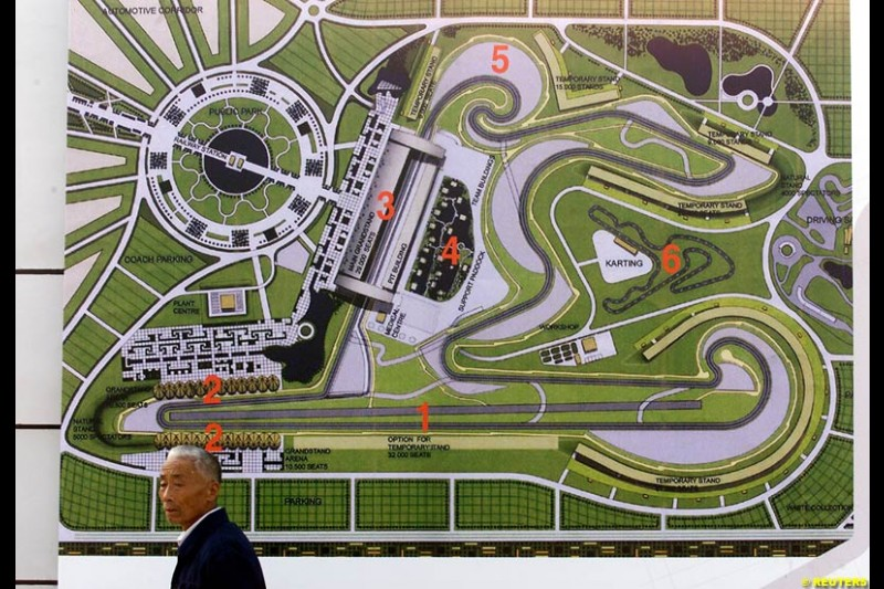 A Chinese resident walks past a floor plan of the Shanghai Circuit during its ground-breaking ceremony October 17, 2002. Shanghai has begun work on a 5.45-km (3.39-mile) racetrack north of the city, designed to look like the first Chinese character in the city's name and quot;shang and quot;.