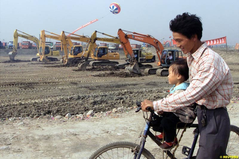 A Chinese father and child pass heavy machines rolling during the Shanghai Circuit ground-breaking ceremony October 17, 2002.