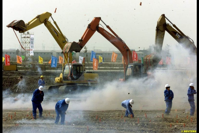 Chinese workers light firecrackers as heavy machines rev their engines during the Shanghai Circuit ground-breaking ceremony October 17, 2002.