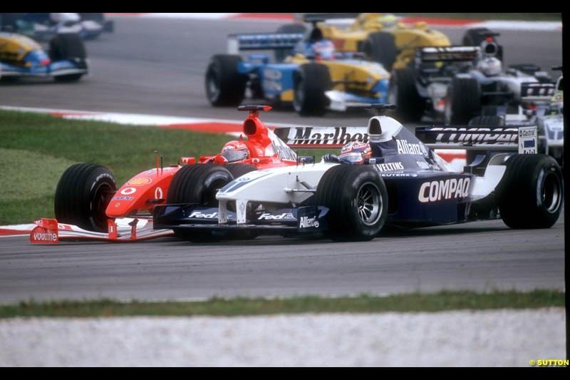 Juan Pablo Montoya, Williams, and Michael Schumacher, Ferrari, tangle during the Malaysian Grand Prix, Round 2.